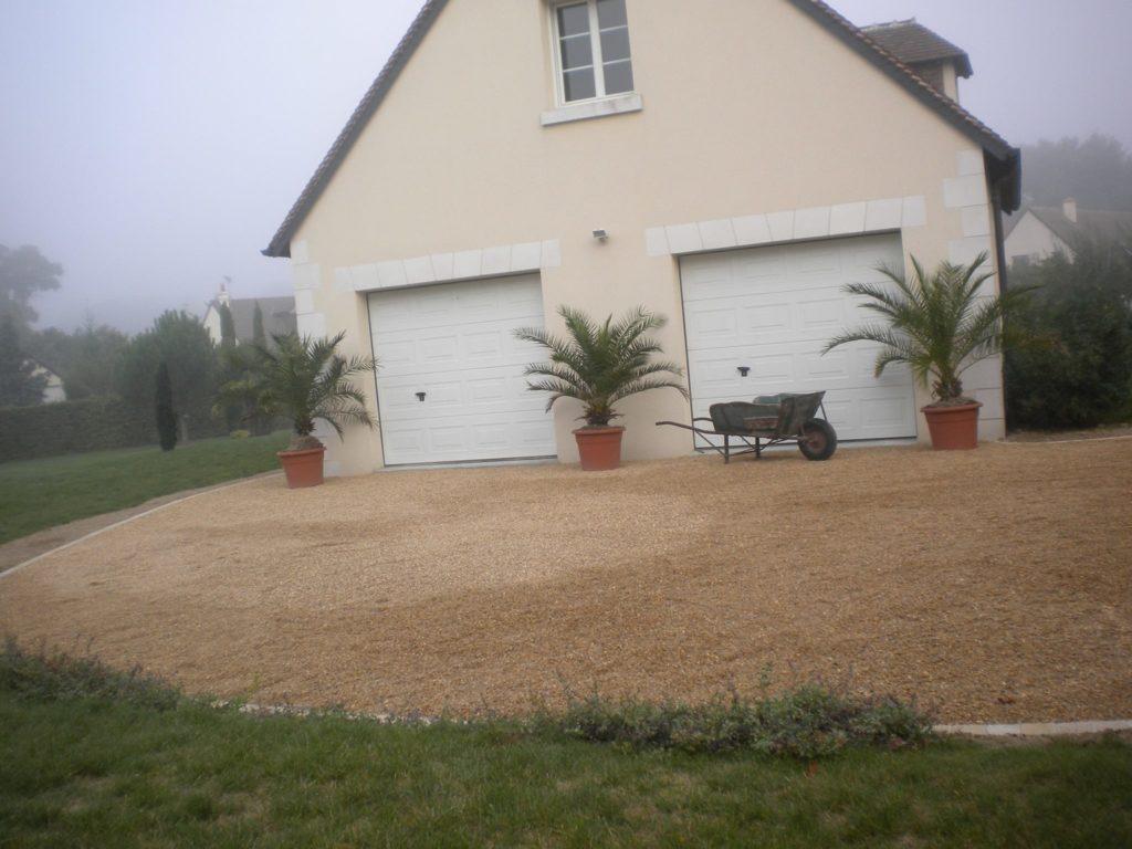 Aménagement d'une allée en gravier devant garages de maison