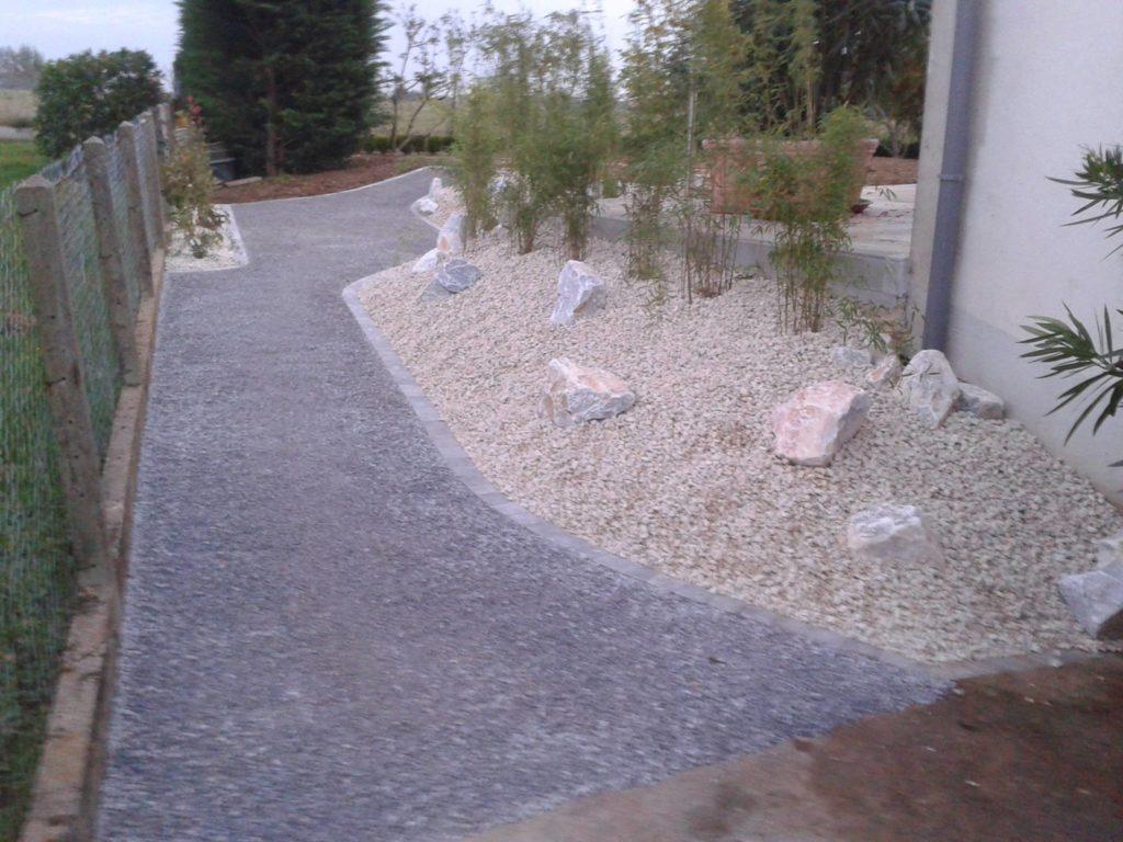 Aménagement d'une allée bétonnée avec des graviers et rochers en décoration par Entre Pierres et Vert