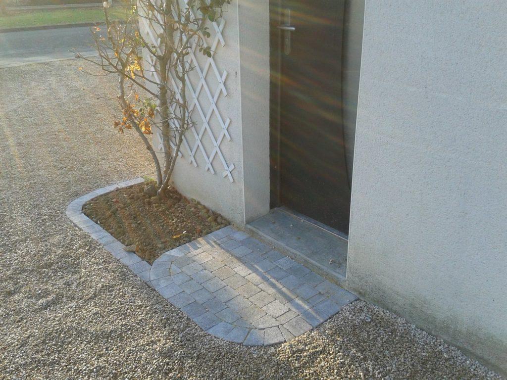 Aménagement d'une allée devant porte d'entrée à l'aide de pavés et graviers par Entre Pierres et Vert