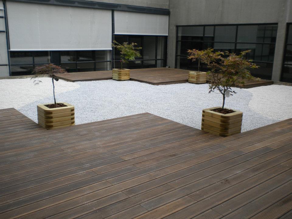 Aménagement paysager avec grande terrasse en bois et graviers par Entre Pierres et Vert
