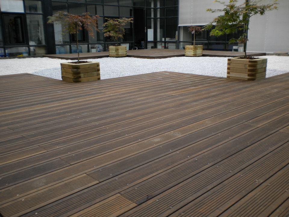 Aménagement paysagers avec grande terrasse en bois et graviers par Entre Pierres et Vert