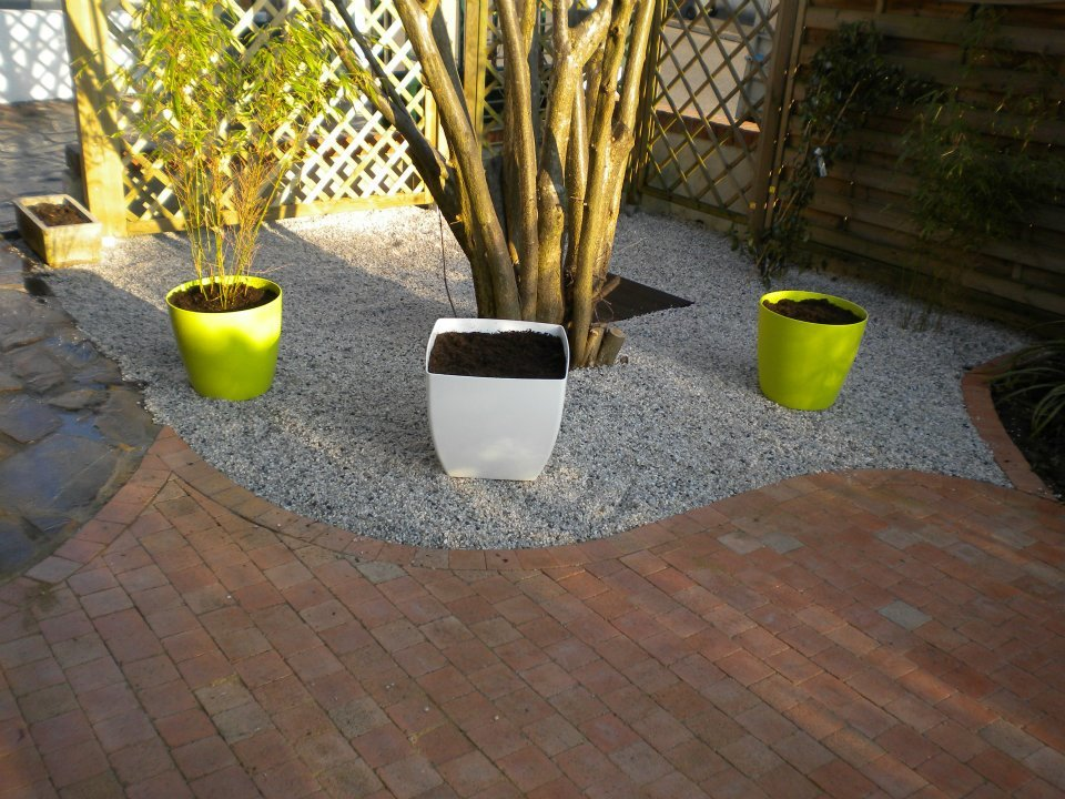 Création d'une terrasse et aménagement paysager à l'aide de graviers et plantes en pot par Entre Pierres et Vert